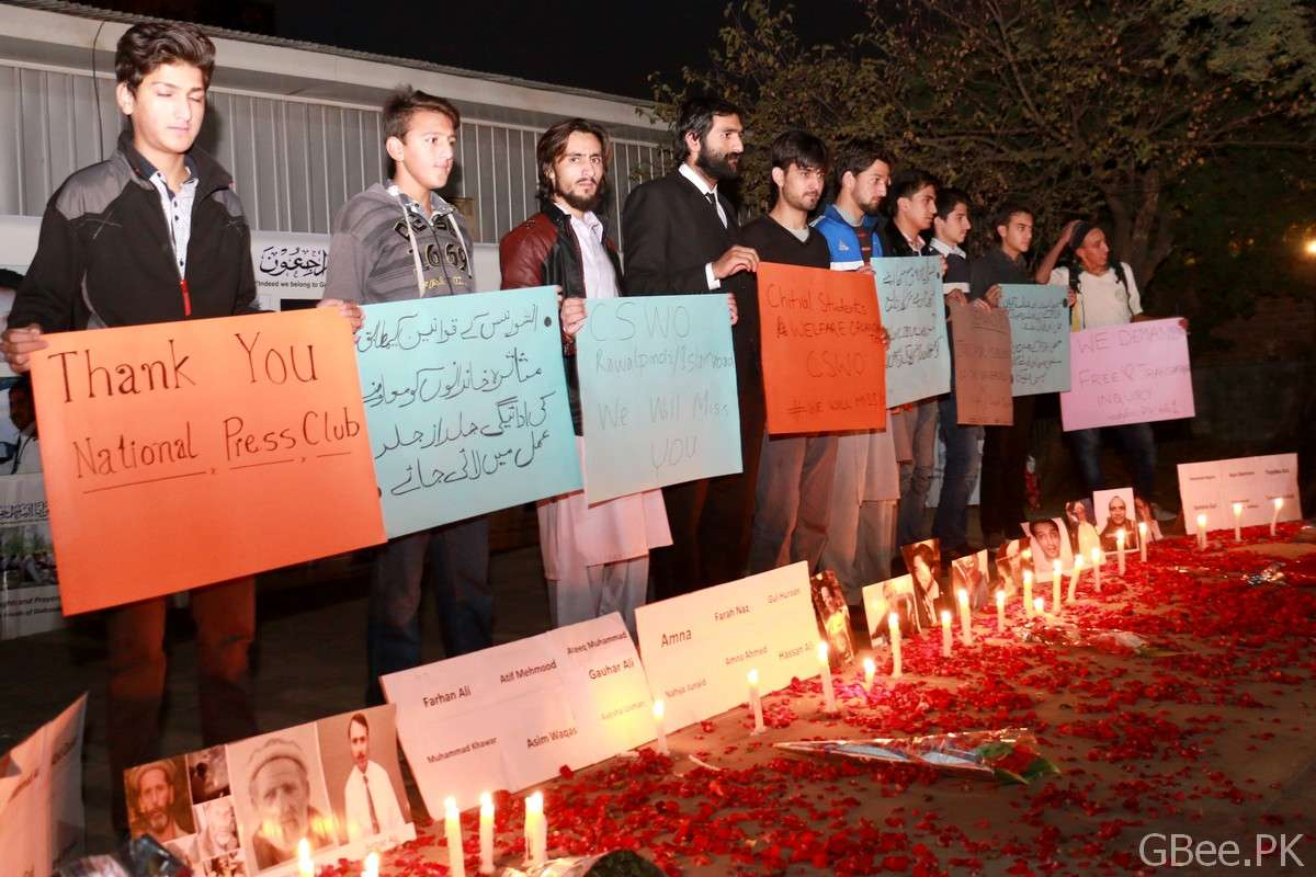 Members of Chitral Students Federation holding banners during candlelight vigil outside Islamabad Press Club